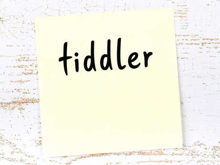 Concept of reminder about tiddler. Yellow sticky sheet of paper on wooden wall with inscription