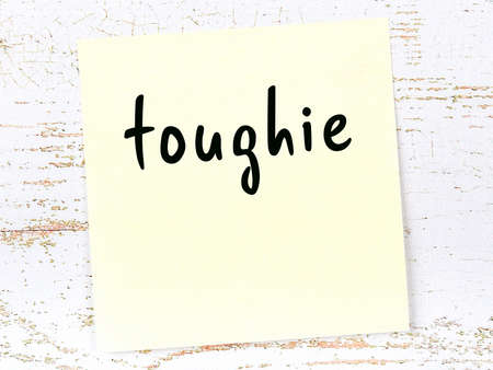 Concept of reminder about toughie. Yellow sticky sheet of paper on wooden wall with inscription Standard-Bild
