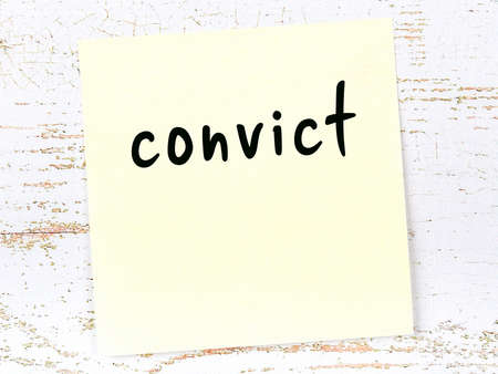 Yellow sticky note on wooden wall with handwritten inscription convict