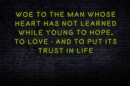 Wise quotation as light neon sign on brick wall