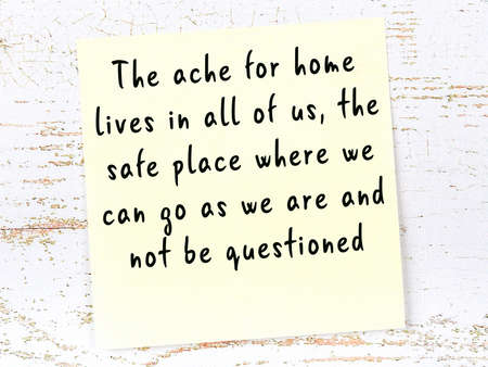 Yellow sticky note with smart quotation handwritten on it hanging on wooden wall Фото со стока