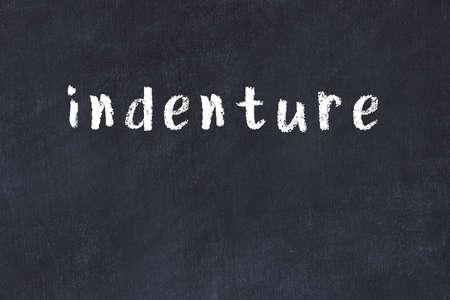 College chalkboard with with handwritten inscription indenture on it Standard-Bild