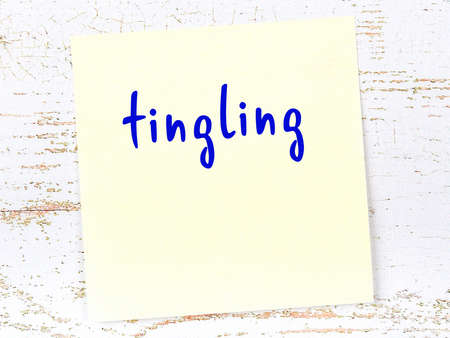 Concept of reminder about tingling. Yellow sticky sheet of paper on wooden wall with inscription Banco de Imagens
