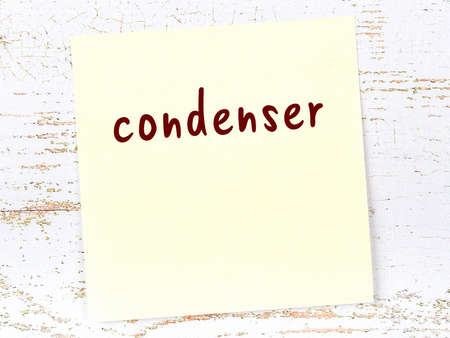 Concept of reminder about condenser. Yellow sticky sheet of paper on wooden wall with inscription