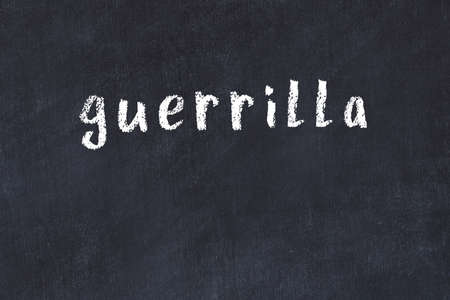 Chalk handwritten inscription guerrilla on black desk
