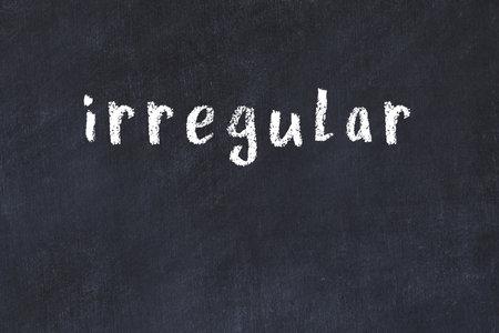 Chalk handwritten inscription irregular on black desk Standard-Bild
