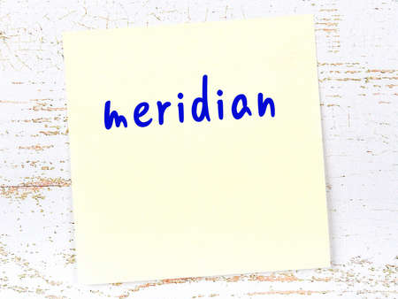 Concept of reminder about meridian. Yellow sticky sheet of paper on wooden wall with inscription