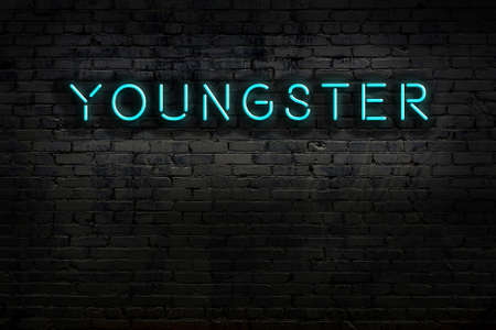 Neon sign on brick wall at night. Inscription youngster