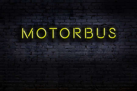 Neon sign on brick wall at night. Inscription motorbus