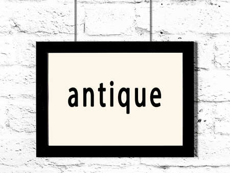 Black wooden frame with inscription antique hanging on white brick wall