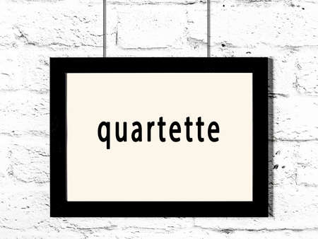 Black wooden frame with inscription quartette hanging on white brick wall