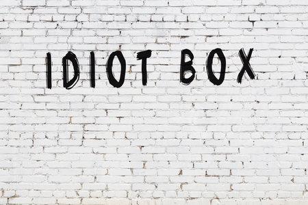Inscription idiot box written with black paint on white brick wall. Фото со стока
