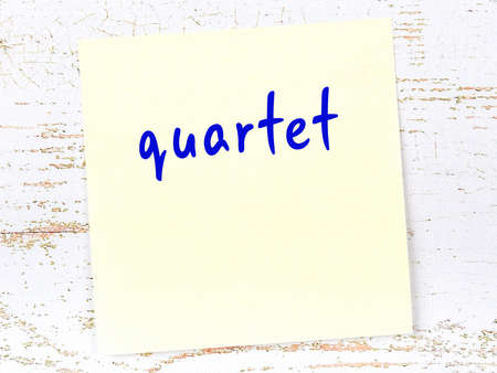 Concept of reminder about quartet. Yellow sticky sheet of paper on wooden wall with inscription