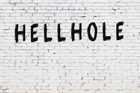 Inscription hellhole written with black paint on white brick wall.