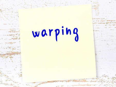 Concept of reminder about warping. Yellow sticky sheet of paper on wooden wall with inscription Stock fotó