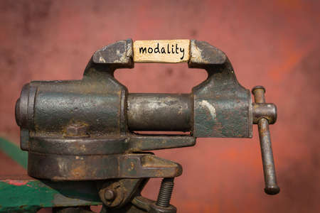 Concept of dealing with problem. Vice grip tool squeezing a plank with the word modality