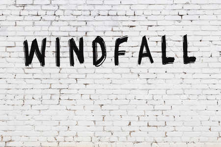 White brick wall with inscription windfall handwritten with black paint