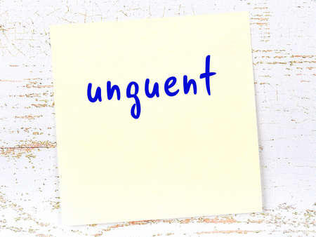 Concept of reminder about unguent. Yellow sticky sheet of paper on wooden wall with inscription