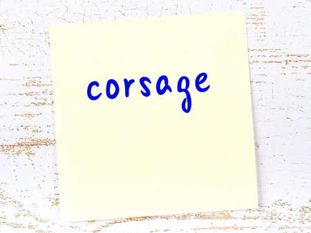 Concept of reminder about corsage. Yellow sticky sheet of paper on wooden wall with inscription