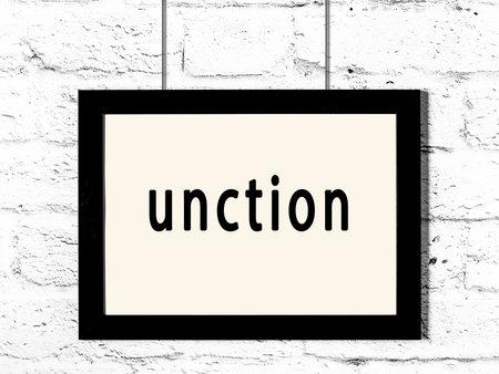 Black wooden frame with inscription unction hanging on white brick wall Reklamní fotografie