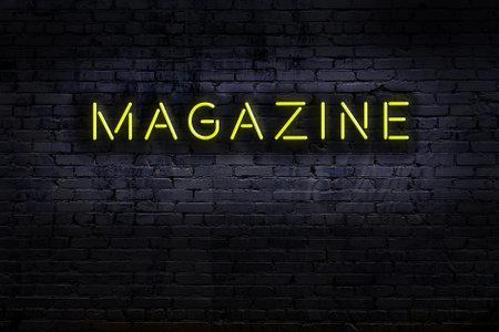 Neon sign on brick wall at night. Inscription magazine
