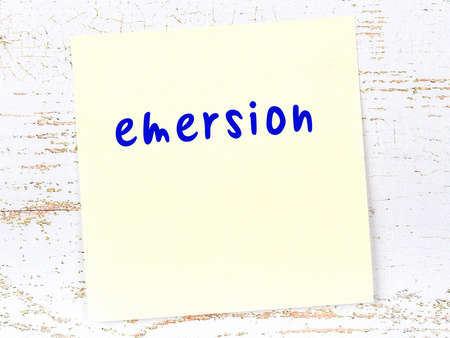 Concept of reminder about emersion. Yellow sticky sheet of paper on wooden wall with inscription