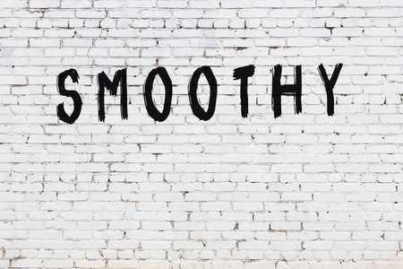 Inscription smoothy written with black paint on white brick wall.