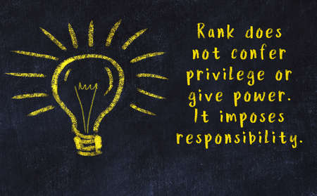 Wise quotation and a chalk drawing of a bulb on black chalkboard Banco de Imagens