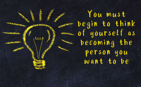 Smart quotation handwritten on a chalkboard and a light bulb sketch Imagens