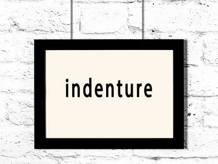 Black wooden frame with inscription indenture hanging on white brick wall Standard-Bild
