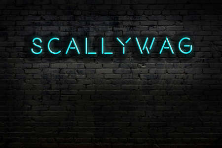Neon sign with inscription scallywag against brick wall. Night view