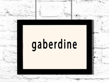 Black wooden frame with inscription gaberdine hanging on white brick wall
