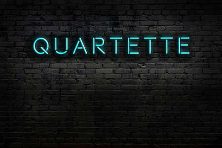 Neon sign on brick wall at night. Inscription quartette
