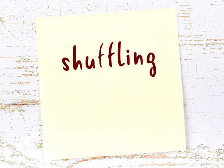 Concept of reminder about shuffling. Yellow sticky sheet of paper on wooden wall with inscription