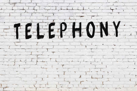 Inscription telephony written with black paint on white brick wall.