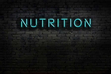 Neon sign on brick wall at night. Inscription nutrition
