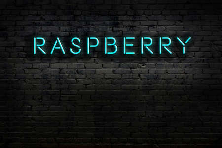 Neon sign on brick wall at night. Inscription raspberry