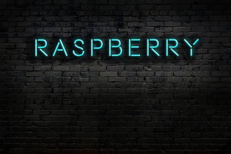 Neon sign on brick wall at night. Inscription raspberry