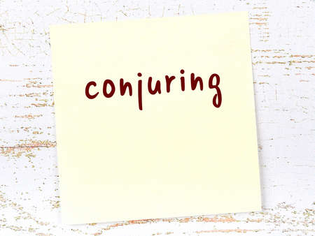 Concept of reminder about conjuring. Yellow sticky sheet of paper on wooden wall with inscription