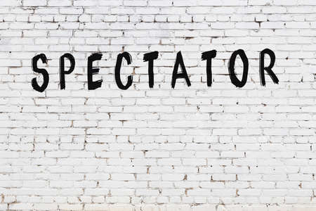 Inscription spectator written with black paint on white brick wall.