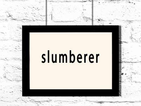 Black wooden frame with inscription slumberer hanging on white brick wall