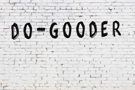 Inscription do-gooder written with black paint on white brick wall. Stock fotó