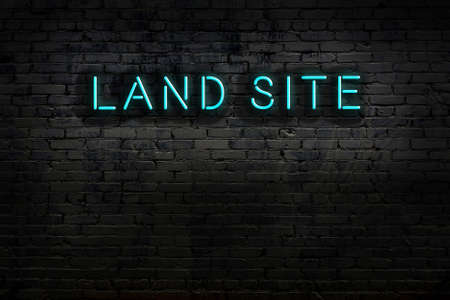 Neon sign with inscription land site against brick wall. Night view Stock fotó
