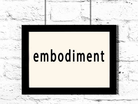 Black wooden frame with inscription embodiment hanging on white brick wall