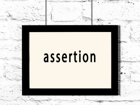 Black wooden frame with inscription assertion hanging on white brick wall