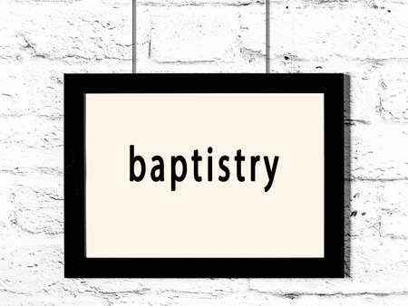 Black wooden frame with inscription baptistry hanging on white brick wall