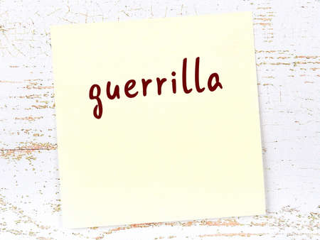 Concept of reminder about guerrilla. Yellow sticky sheet of paper on wooden wall with inscription