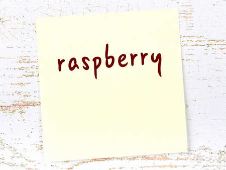 Yellow sticky note on wooden wall with handwritten inscription raspberry