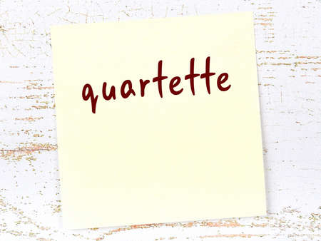 Concept of reminder about quartette. Yellow sticky sheet of paper on wooden wall with inscription