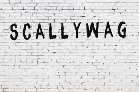 White brick wall with inscription scallywag handwritten with black paint